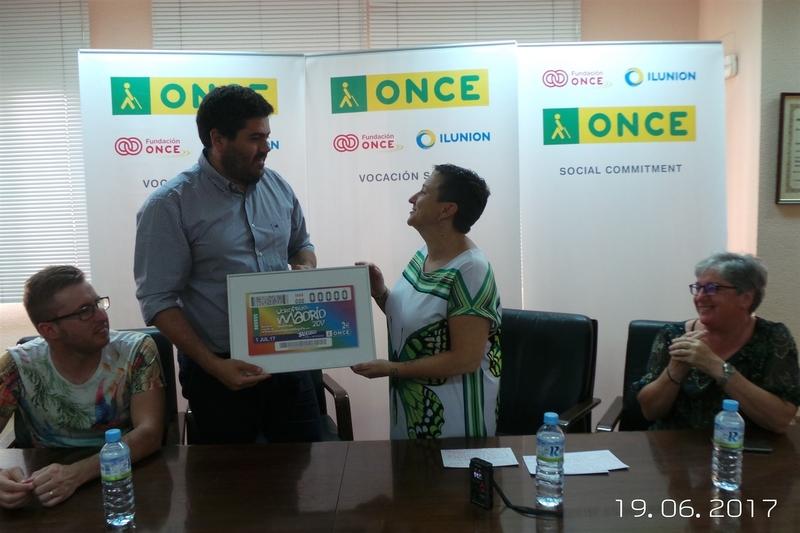 La ONCE entrega a la presidenta de Extremadura Entiende una lámina enmarcada del cupón dedicado al WorldPride Madrid